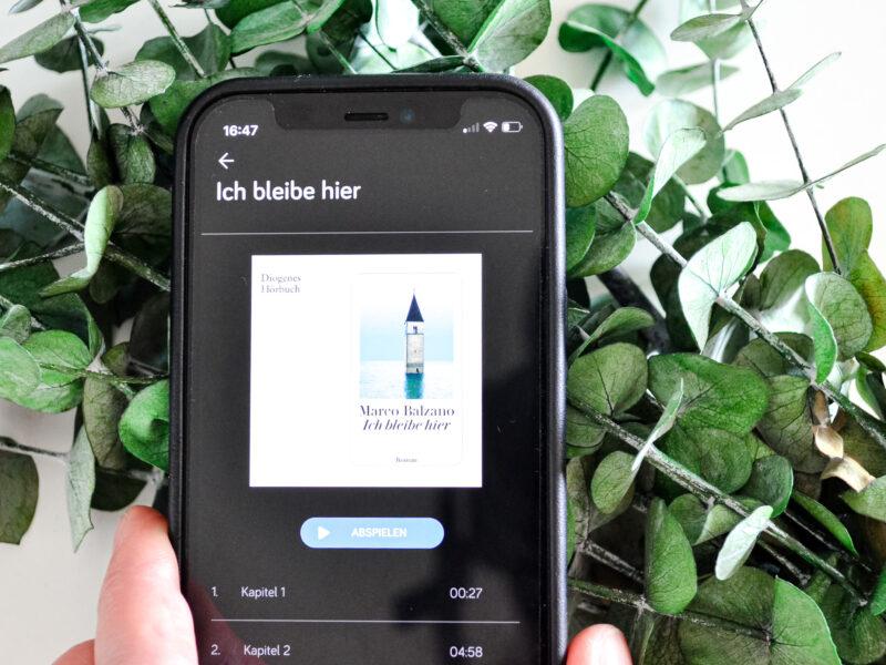 Smartphone vor Eukalyptus, das Cover des Buches auf dem Bildschirm